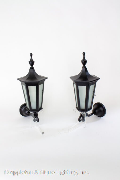 Early 20th Century black lantern sconces. Painted cast iron backplate and frame, with frosted glass panels. Open at the bottom for access to lightbulb. Porcelain socket.